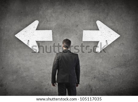 Young businessman standing in front of two arrows showing two different directions - stock photo