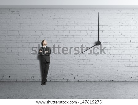 young businessman standing in loft and clock in wall - stock photo