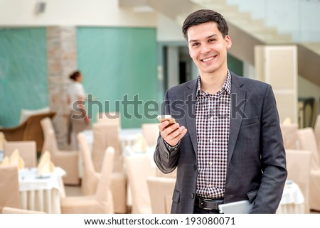 Young businessman standing in office and talking on the phone. Young and successful man solves problems in a business meeting. The guy looks straight into the camera and smiling - stock photo