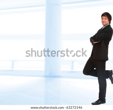 Young businessman standing in office lobby - stock photo