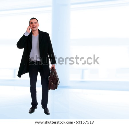 Young businessman standing in office lobby talking on the phone - stock photo
