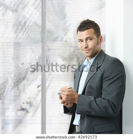 Young businessman standing in office lobby, using smartphone, smiling. - stock photo