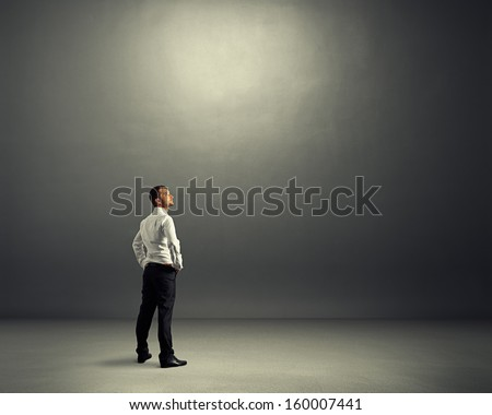 young businessman standing in the dark grey room and looking up - stock photo