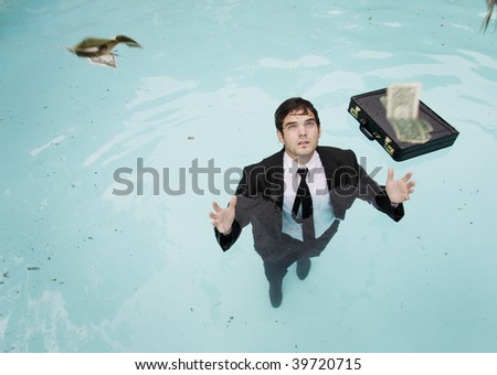 Young businessman standing in water, reaching for falling money.