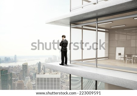 young businessman standing near office and thinking - stock photo