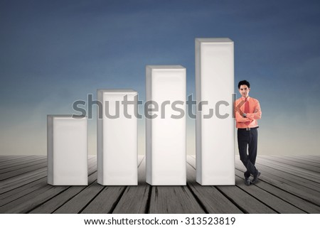 Young businessman standing next to growing bar chart on blue sky background - stock photo