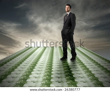 Young businessman standing on a euro banknotes floor