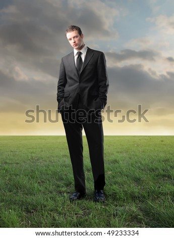 Young businessman standing on a green meadow - stock photo