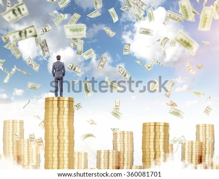 Young businessman standing on a pile of golden coins, proud of himself, other piles around, dollars falling from above. Blue sky at the background. Concept of earning money and prosperity. - stock photo