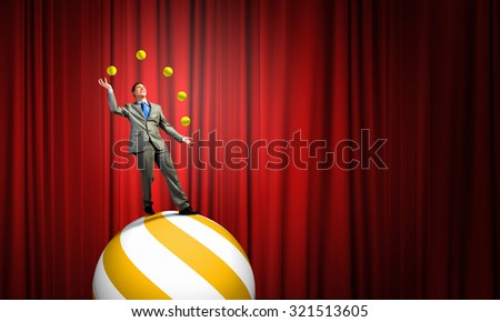 Young businessman standing on ball juggling with balls - stock photo