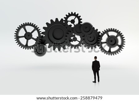 Young businessman standing on cog wheel elements - stock photo