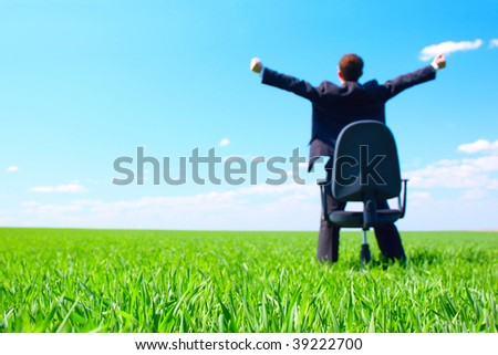 Young businessman standing on green field near chair. Focus on grass - stock photo