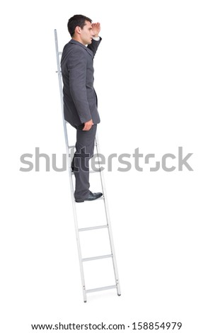 Young businessman standing on ladder looking away on white background