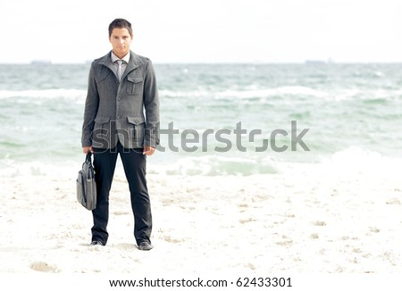 Young businessman standing on the beach