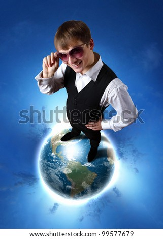 Young businessman standing on the planet earth model - stock photo