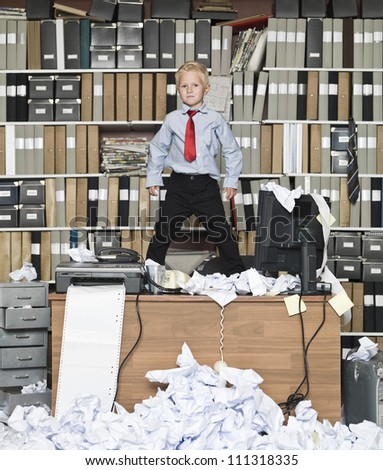 Young businessman standing on the table in a messy office