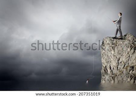 Young businessman standing on top of rock and fishing - stock photo