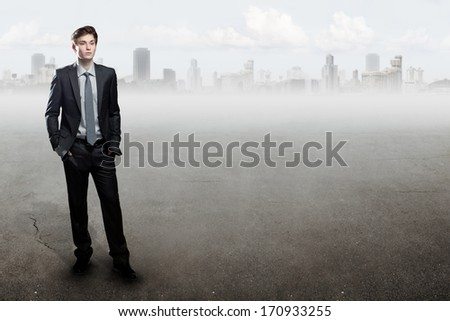 Young  businessman standing over city background. With place for text. - stock photo