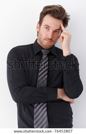Young businessman standing over white background, thinking. - stock photo
