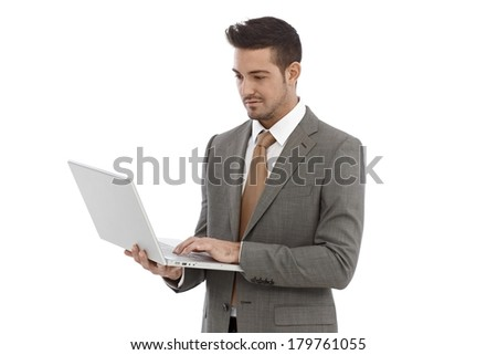 Young businessman standing over white background using laptop computer, holding in hand. - stock photo