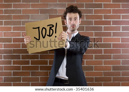 "Young businessman standing pleading with sign ""Need Job"""