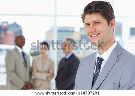 Young businessman standing upright with his team between him - stock photo