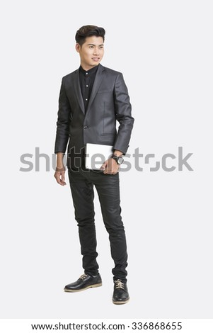 Young businessman standing  with digital tablet on white background. - stock photo