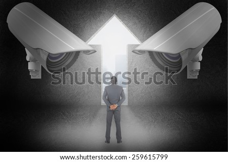 Young businessman standing with hands behind back against light bulb graphic on futuristic background