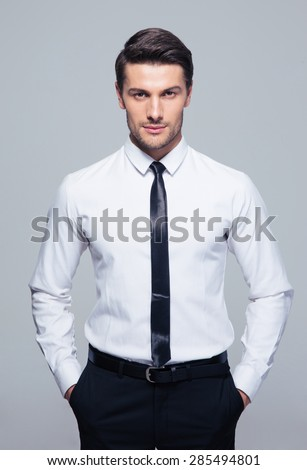 Young businessman standing with hands in pocket over gray background - stock photo
