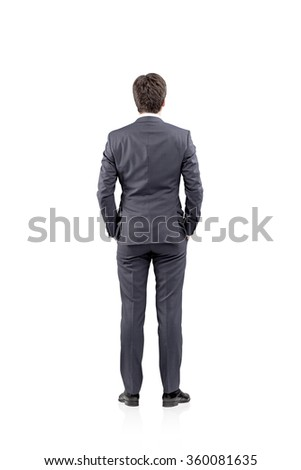 Young businessman standing with his hands in pockets. Back view. Concept of thinking - stock photo