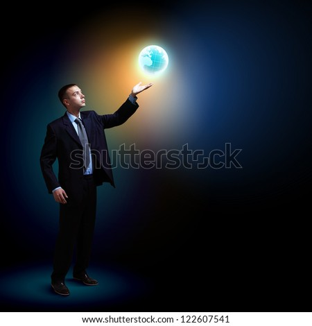 Young businessman standing with our planet Earth. - stock photo
