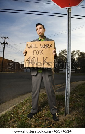 Young businessman stands on a street corner, holding a sign that reads 'will work for 401 K'. Vertical shot. - stock photo