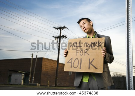 Young businessman stands on a street corner holding a sign that reads 'will work for 401 K'. Horizontal shot. - stock photo