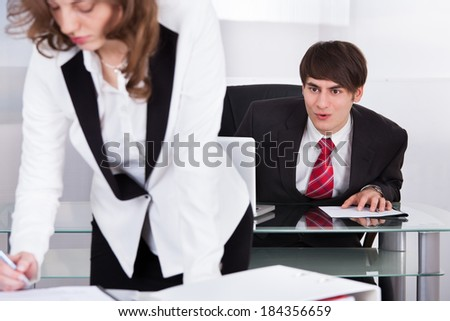 Young businessman staring at woman's back in office - stock photo