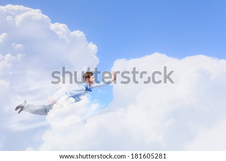 Young businessman superhero flying high in sky - stock photo
