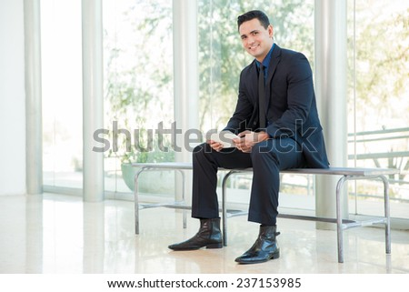 Young businessman taking a break and doing some social networking on his tablet computer at work - stock photo