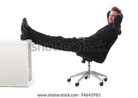 Young businessman taking a break, resting with legs on desk, smiling.? - stock photo