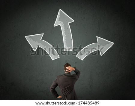 Young businessman taking a decision with different directed arrows above his head - stock photo