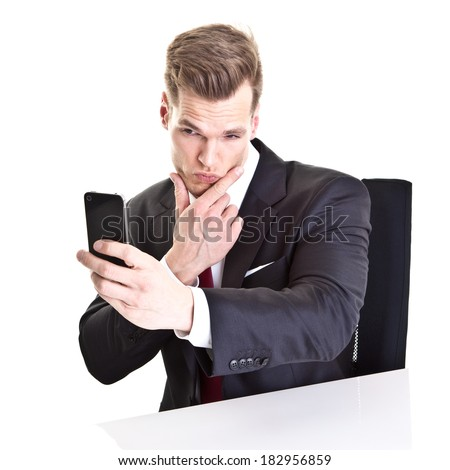 Young businessman taking a selfie with his smartphone - isolated on white - stock photo