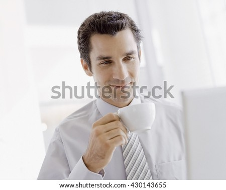 Young businessman taking a sip of coffee next to his laptop