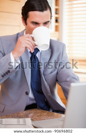 Young businessman taking a sip of coffee next to his laptop - stock photo