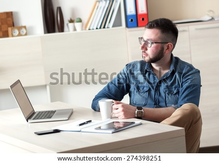 Young businessman taking coffee break in his office. - stock photo