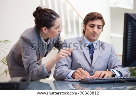 Young businessman taking notes while getting explanation by colleague