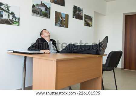 Young Businessman Taking Rest at the Office with Feet on the Wooden Table While Leaning on the Wall. - stock photo