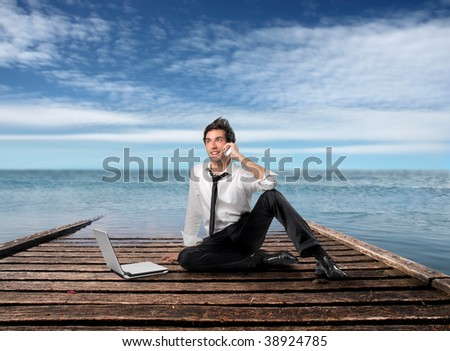 young businessman talking at mobile phone and using laptop on a wharf - stock photo