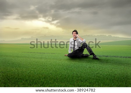 young businessman talking at mobile phone in a grass field