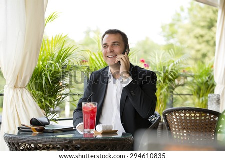 Young businessman talking on a cell phone and drinking a cocktail sitting in a summer restaurant - stock photo