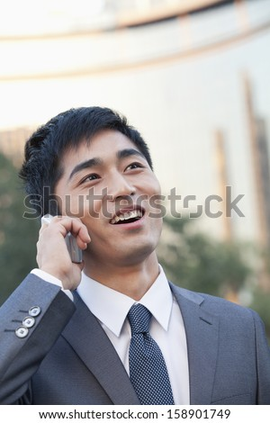 Young businessman talking on cell phone - stock photo
