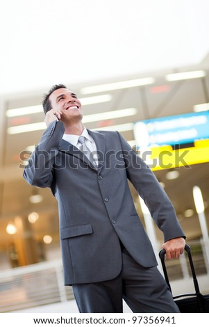 young businessman talking on cellphone at airport