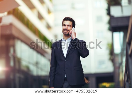 Young businessman talking on his phone outdoors